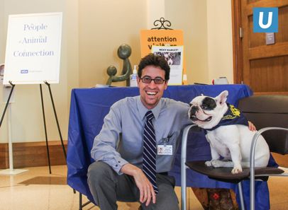 Dr. Andrew Leitner, resident fellow in anesthesiology, UCLA Medical Center, Santa Monica, spends a moment with Harley, PAC dog, during his visit.
