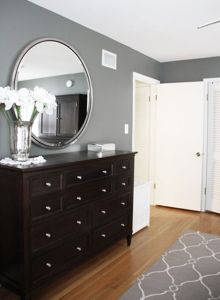 Benjamin Moore Amherst Gray in this bedroom with a gray and white patterned rug, white trim and dark wood furniture.