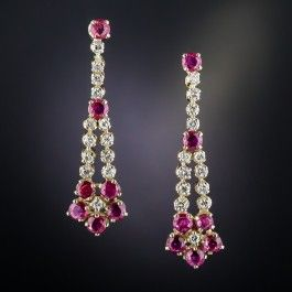 1 and 3/8 inches inch long and lovely ear drops aglitter with bright-white and sparkling round brilliant-cut diamonds and bright red faceted round rubies culminating in a classic flower blossom motifs. Utterly delightful estate jewels hand fabricated in gleaming 10K yellow gold.