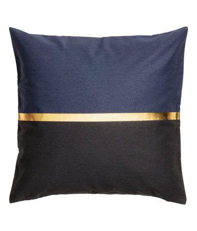 Dunkelblau/Schwarz. Kissenhülle aus Baumwolltwill mit Blockmuster und aufgedrucktem goldfarbenem Streifen. Verdeckter Reißverschluss.