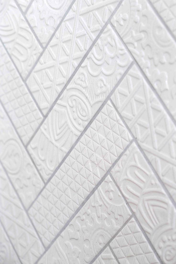 De wandtegels met kantreliëf zijn een lust voor het oog. Het mixen van het wildverband patroon op de vloer en het visgraatpatroon aan de wand zorgen voor een prachtige ambiance.