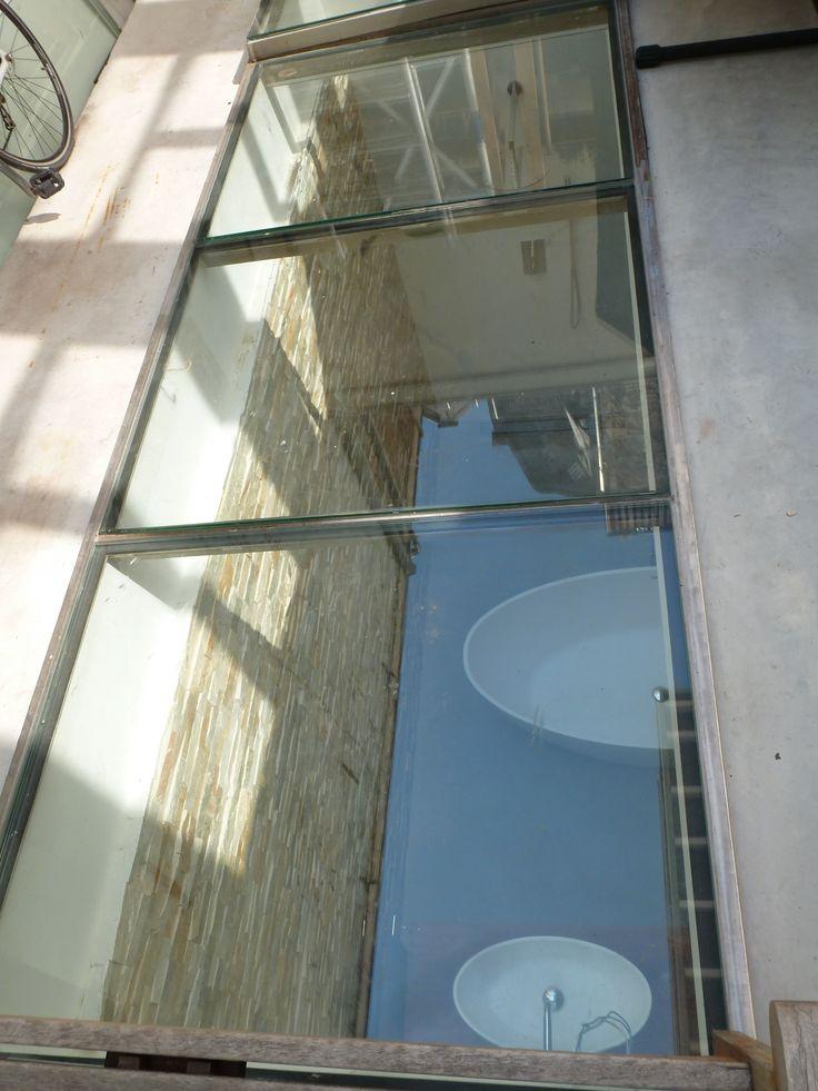 Glazen doorkijk naar badkamer in souterrain te Amsterdam   BNLA architecten