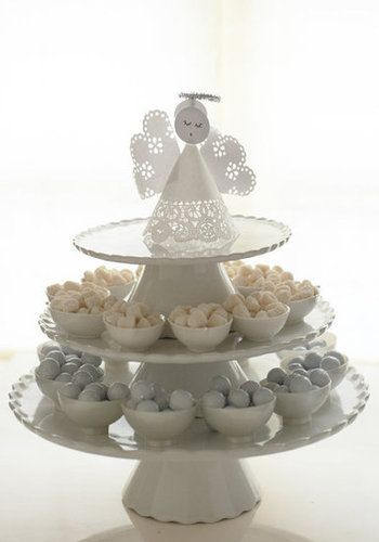 A tiered cake stand and little bowls with candy, topped with a paper angel, make a great centerpiece. To create the angel, simply use a doily for the body, a circle edge punch to edge the wings, and a doily punch to edge the angel's body.  Source: Martha Stewart Living  I  Photography by Charlotte Jenks Lewis