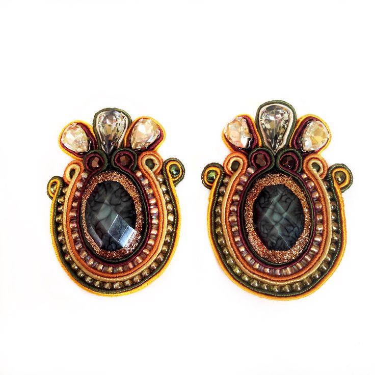 Statement earrings handmade using the soutache embroidery technique with soutache braids in autumn colours of pale gold, rust, orange, olive green, brown.Also used for making of these earrings were glass round Toho beads in lustre olivine, matte green olive, green, gold lined rainbow and faceted bronze beads.Main stone is marbled charcoal resin cabochon with gold glitter outline, above it are two pear chaped crystal golden shadow glass stones and black diamond glass tear drop ...