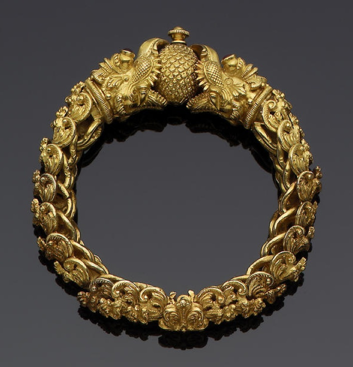 A gem-set gold Bracelet Tamil Nadi, first half of 20th Century comprising interlinking elements in the form of floral kirttimukhas, the termimals in the form of makara heads, holding an orb between their open mouths, the eyes gem-set 9 cm. diam. approx.