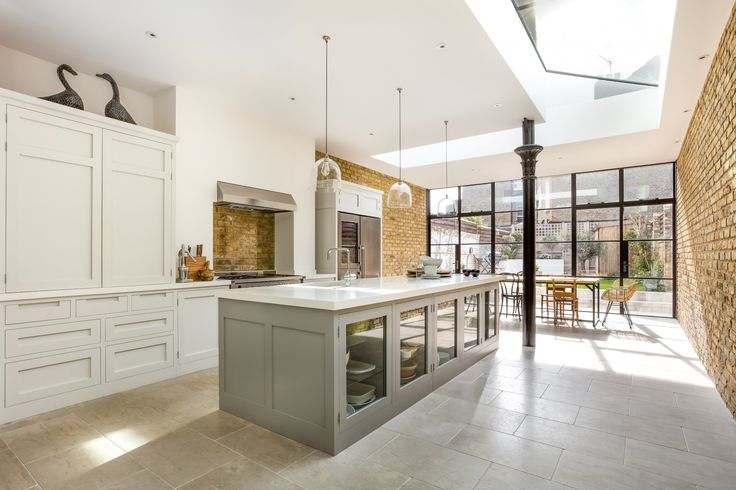 Higham - An amazing handleless shaker kitchen, corian worktops in a room with Crittal doors and exposed brickwork