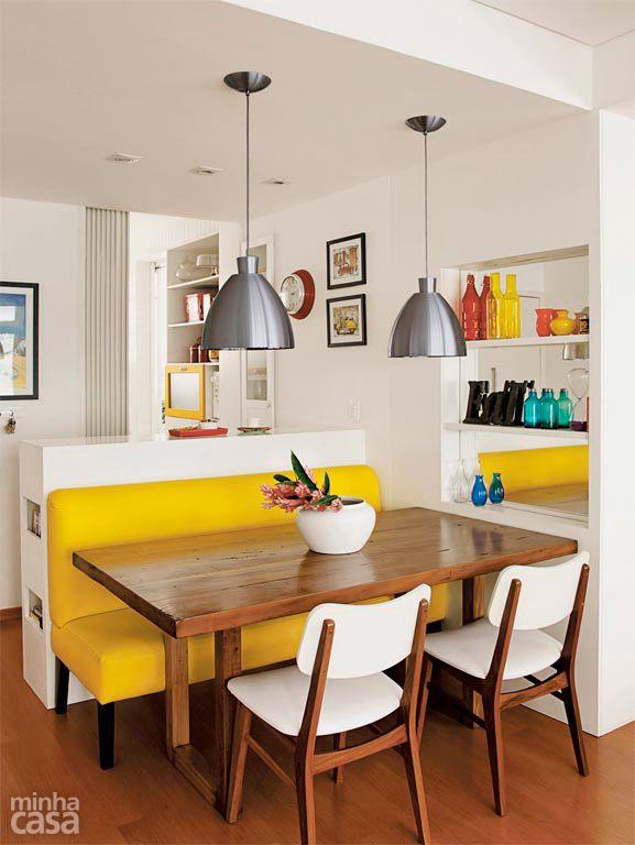 Nesta área de refeições, um sofá amarelo de couro sintético é o destaque da decoração. A mesa de cadeira maciça é servida por cadeiras, que acrescentam branco à combinação quente. Uma estante embutida, com fundo espelhado, amplia visualmente este canto.