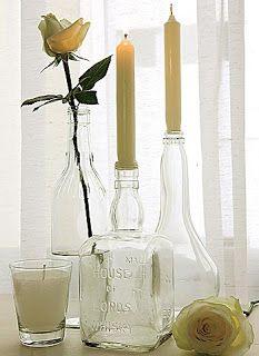 Castiçais com garrafas de vidro.