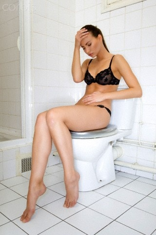 Young woman sitting on toilet holding stomach | Graphics