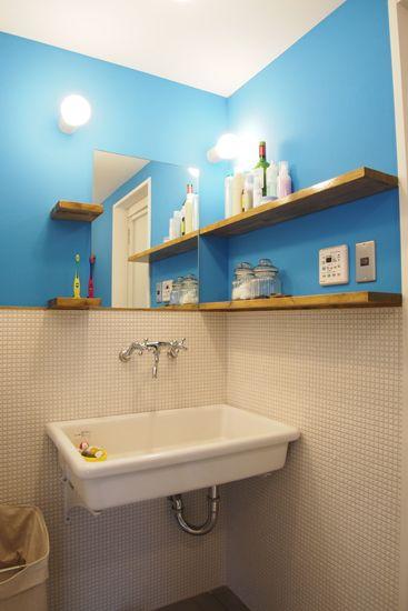 ライトブルーの壁と白いモザイクタイルが爽やかな洗面所。…