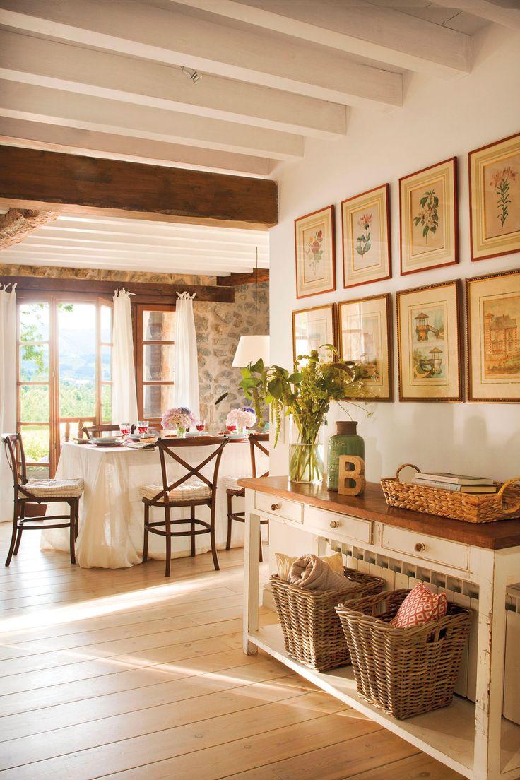 Zona de paso hacia el comedor con consola blanca y composición de cuadros