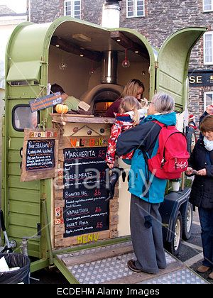 Street food vendor selling pizza from a converted horse trailer at the Padstow Christmas festival, Cornwall, UK Stock Photo