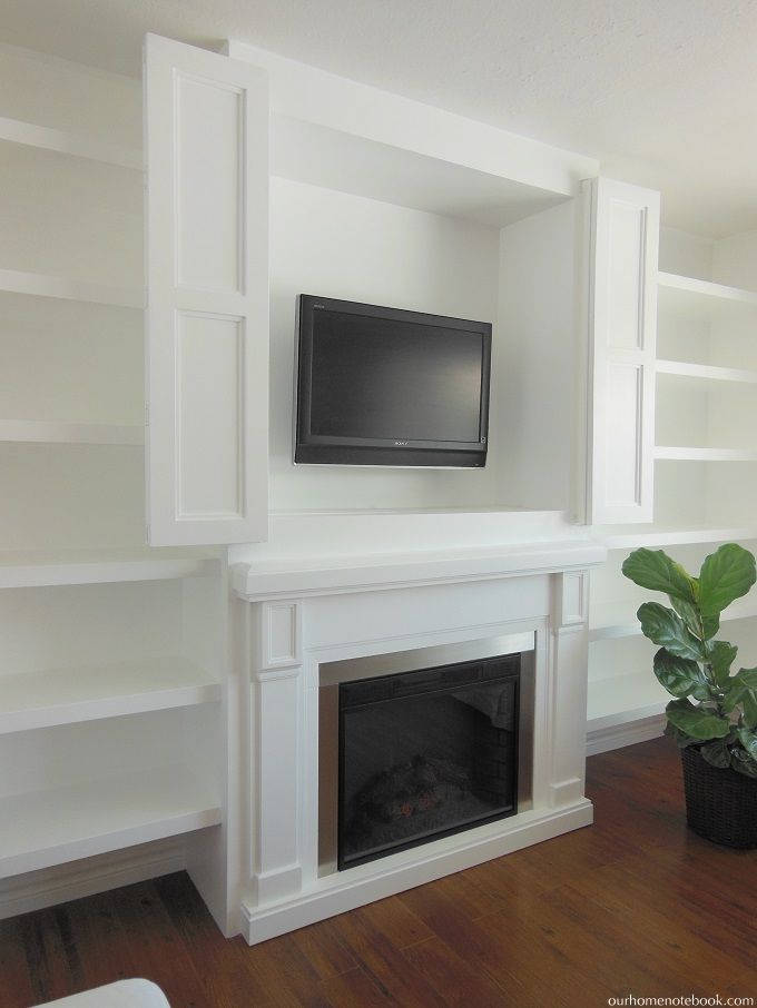 Built-in TV nook over fireplace with bi-fold doors to hide media when it's not in use.