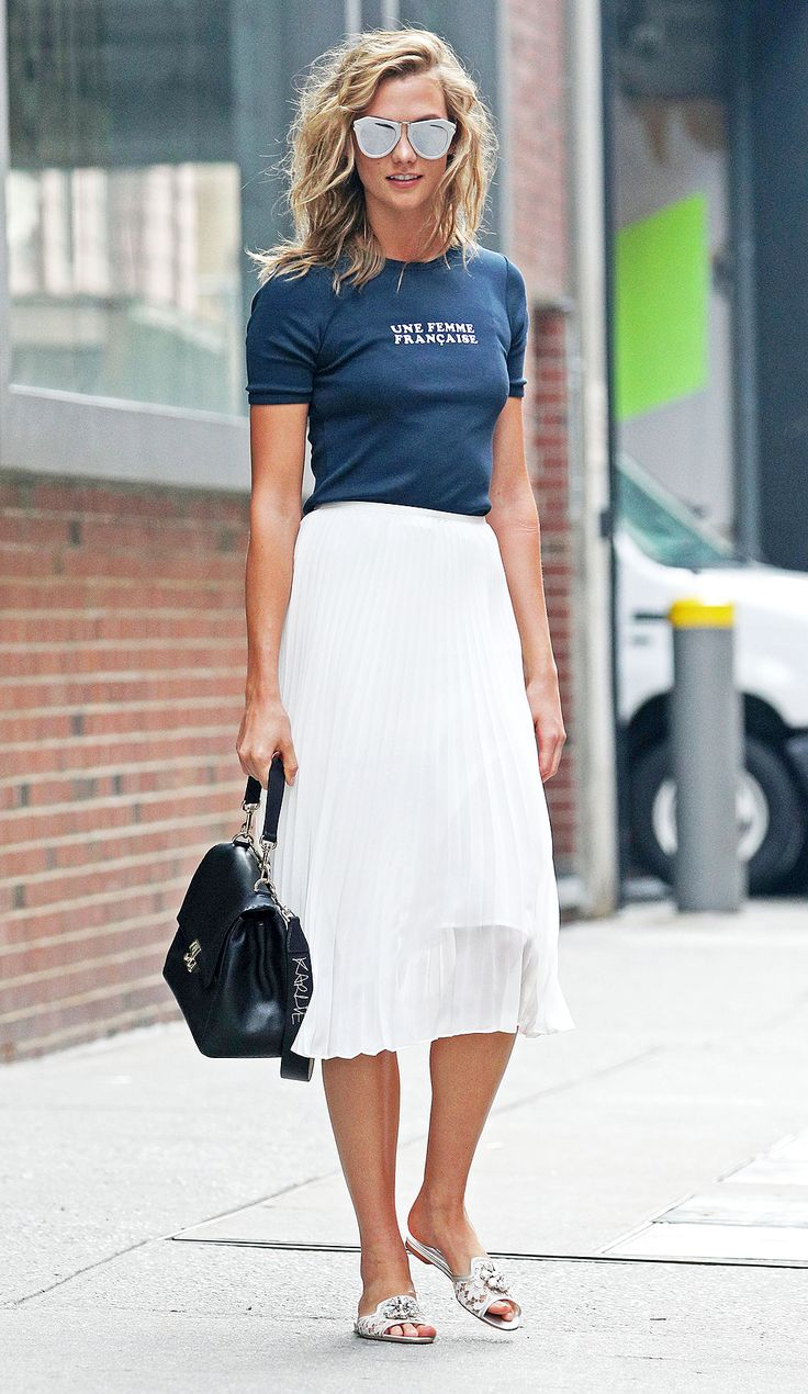 Karlie Kloss in a Veronica Seward tee, Babaton for Aritzia pleated skirt and Dolce and Gabbana slides with a Carolina Herrera bag and Karen Walker sunglasses - click through for more flats outfit ideas from the model!