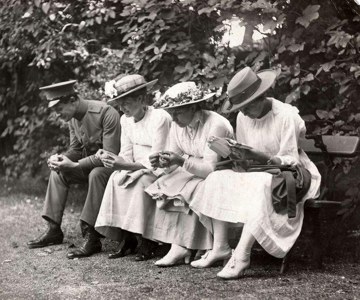 Artis. [lente.] Bezoekers van de dierentuin: drie jonge vrouwen met hoeden en in witte kleding op een bankje en naast hen een jongeman in uniform. Amsterdam, 1917.