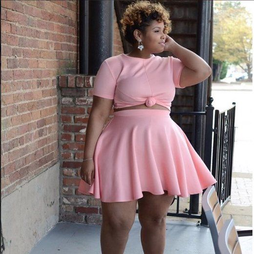 Fierce curvy girl rocks pink crop top, skirt combo.   Essence.com
