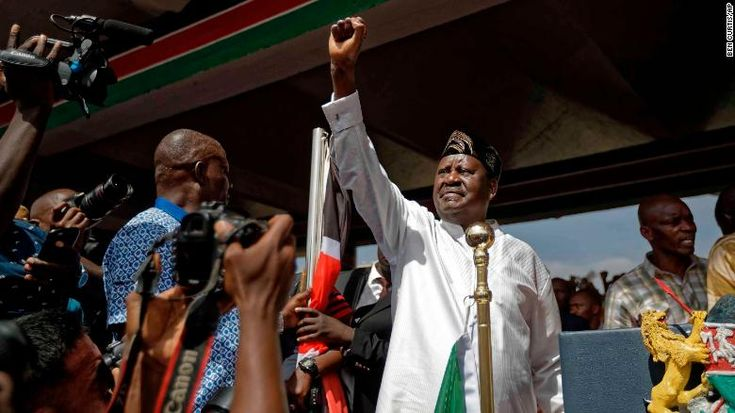 KENYA, Nairobi - Kenya TV stations still off air despite court order - February 2, 2018.  Opposition leader Raila Odinga holds a Bible aloft after swearing an oath during a mock inauguration ceremony at Uhuru Park in downtown Nairobi on Tuesday.