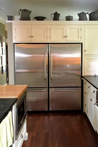 This is a cheap solution: buy 2 identical fridge/freezer combo's. Just make sure the door can be hinged on both sides. Then you can make them look like one commercial fridge.