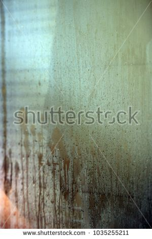 Taking shower, glass shower door with steam and water running down.
