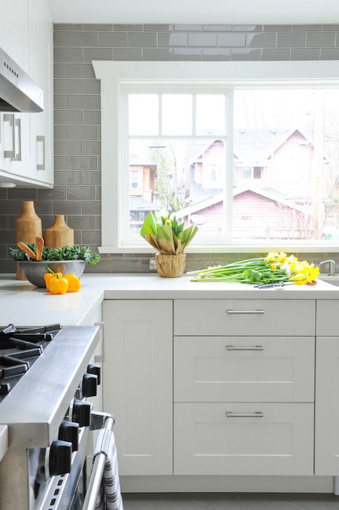 White and gray kitchen features white cabinets paired with white marble countertops and a gray subway backsplash.