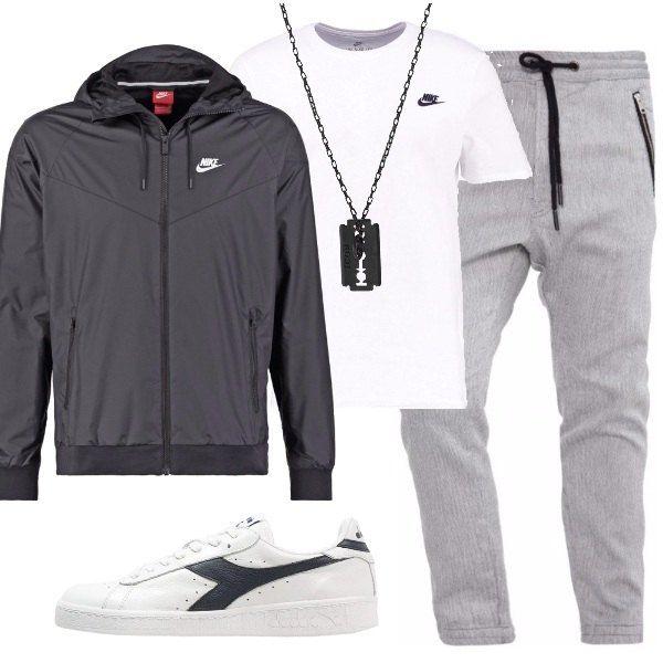 Look casual sui toni del grigio, composto da pantalone sportivo grigio, t-shirt basic bianca a maniche corte e giacca nera leggera con cappuccio. Collana in metallo nero e sneakers basse bianche e nere.