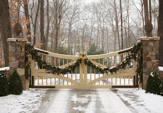 Garland draped on the gate is beautiful during the day, and even better at night when the Christmas lights are on! - Traditional Home ®/ Photo: Michael Partenio / Design: Cindy Rinfret