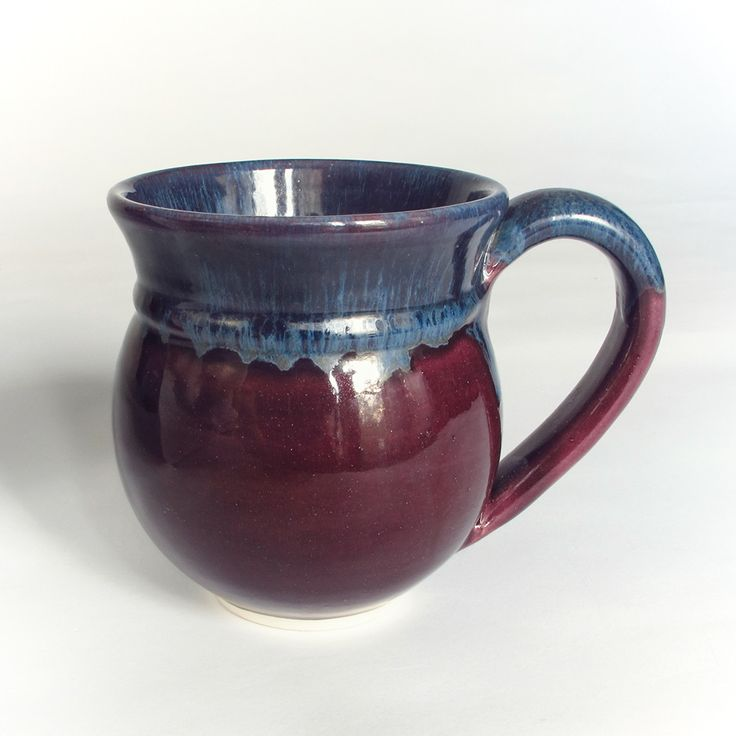 Wheel-thrown and elegantly shaped white earthenware eggplant / orchid purple mug with a handmade handle attached. Glazed with an Aubergine Eggplant Purple lavender blush glaze and blue sea-froth on th