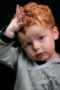 The face of a toddler with red hair, against black background.  Reminds me go GRGC