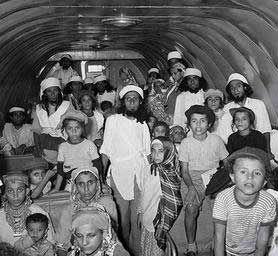 """Image of Yemenite families escaping to Israel in Operation Magic Carpet. 1922, Yemen reintroduced an Islamic law requiring Jewish orphans under age 12 be forcibly converted to Islam.  In 1947 Muslim rioters engaged in a bloody pogrom killing 82 Jews and destroying Jewish homes. In 1948 the false accusation of blood libel led to looting of Jewish homes. Virtually the entire Yemenite Jewish community - almost 50,000 - escaped Yemen between June 1949 and September 1950 in Operation """"Magic…"""