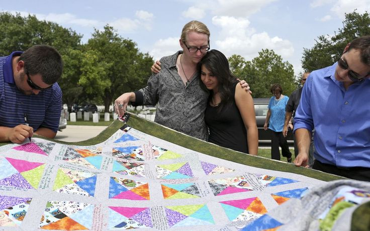Mourners including Jake Hixson (far right), who was to be Thomas Spitzer's best man at his 2015 wedding, read messages directed to Spitzer's fiancée on a quilt made by Brianna Smith.