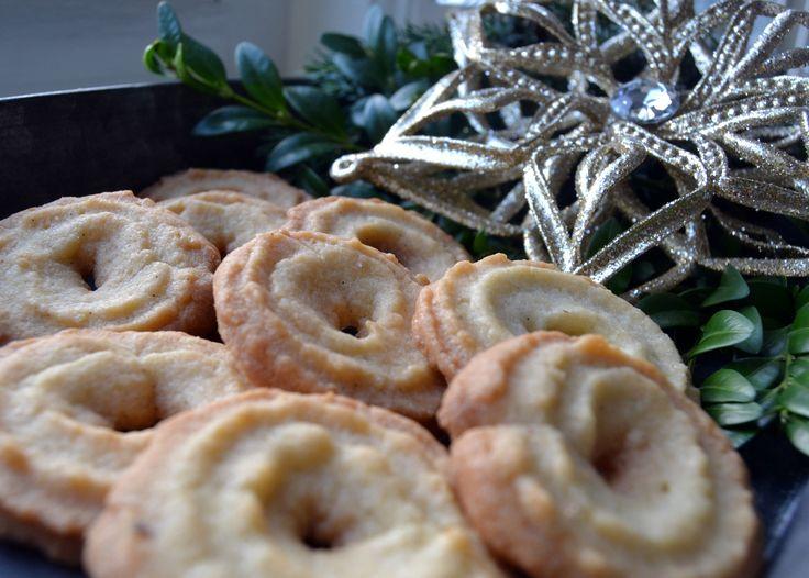 Ingen jul uden vanillekranse – eller brunkager for den sags skyld, men de kommer på bloggen en anden dag. I dag drejer det sig nemlig om de små vanilleprikkede og smørduftende kranse. Og hvad kan vel være hyggeligere, på sådan en regnfuld og ruskende 2. søndag i advent, end at sidde lunt og godt inden …