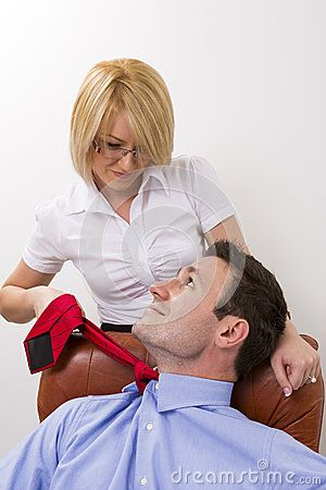Businesswoman seducing her manager at office, pulling up his necktie.
