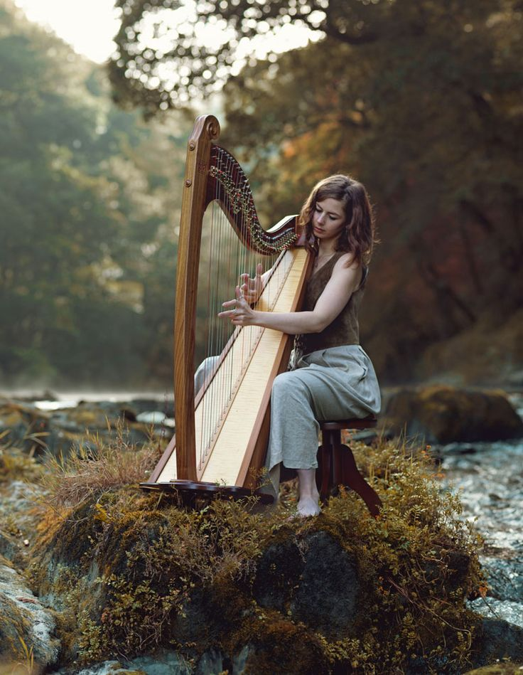Girl playing harp at Cenarth falls in West Wales