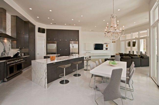 A modern berendezések közül rögtön szemet szúr a gyönyörű kristálycsillár, amely feledteti a modern hangulatot és királyi eleganciát közvetít a nappali-konyha-étkező hármasában!