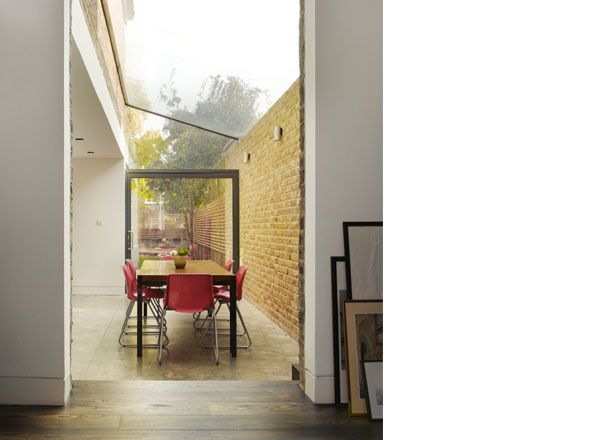 Mapledene Road, Hackney by Platform 5 Architects. The kitchen and patio areas are unified by a concrete floor and London stock brick garden wall. The expansive glass roof opens up the view to the sky giving the space an external character.