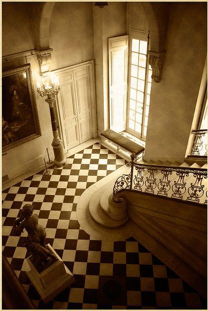 Estilo francés. Detalles de piso compuesto en mosaicos de dos colores, escalera de piedra con baranda de hierro y bronce, puertas francesas.