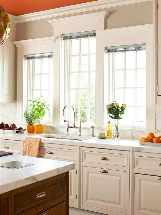 The windows have architectural interest, and I love the wood island with the antique white cabinets. I like the wall color, but I'd choose a different ceiling color.