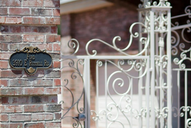 Address placard with white iron wrought gate. Listed by Jeff Biebuyck and Karen Baldwin. Photography courtesy of @Riley Jamison.
