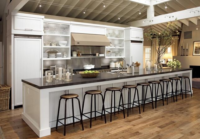 Do you enjoy entertaining? A dramatic, customized island with sink and tasting bar lets the frequent entertainer enjoy her friends while prepping meals in a highly functional space. The Dove White cabinetry and open shelves keep the room airy and uncluttered.