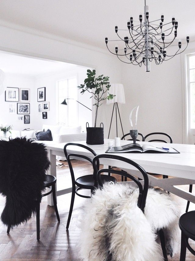This sunlit space features a white table, white walls, black chairs, touches of greenery the the FLOS 2097 pendant lamp.
