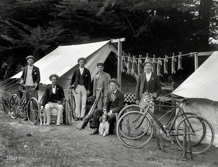 "More morbid bunting: Circa 1910. ""Rabbit-hunting party of six men, with bicycles, guns and dogs, including rabbits strung between two tents. Possibly Christchurch, New Zealand district."" Now where'd we put that cookbook? Glass negative by Adam Maclay."