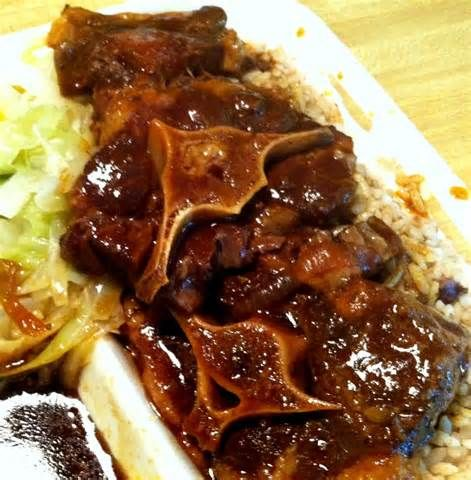 Stew oxtail, on a bed of rice and peas accompanied with steam cabbage
