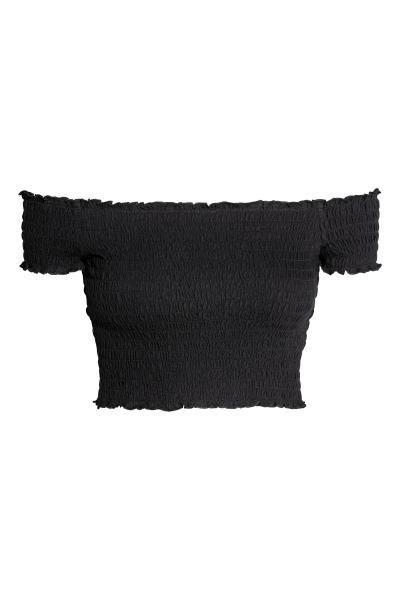 Top corto in jersey di cotone lavorato a smock. Spalle scoperte, maniche corte e bordi a punto overlock.