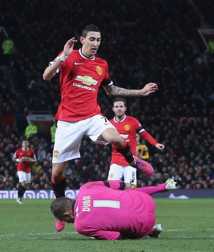 Angel di Maria of Manchester United in action with Chris Dunn of Cambridge United during the FA Cup Fourth Round replay between Manchester United and Cambridge United