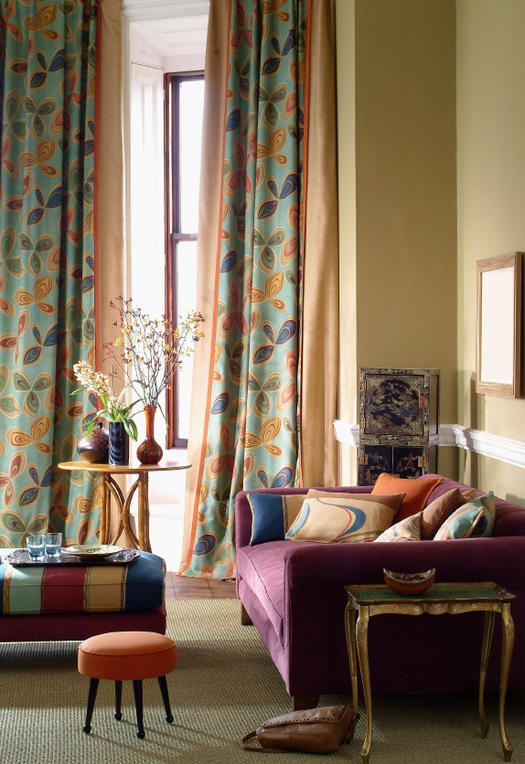Colorful, mod, cozy living room. Love that velvet couch and the bold curtains!