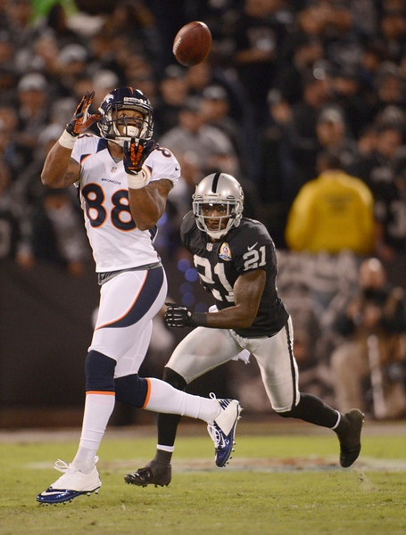 Denver Broncos wide receiver Demaryius Thomas (88) catches a pass on Oakland Raiders cornerback Ron Bartell (21) during the first quarter Thursday, December 6, 2012, during Thursday Night Football at O.c Coliseum in Oakland.