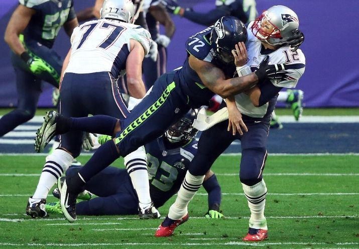 Michael Bennett gets to Tom Brady as he throws the ball.