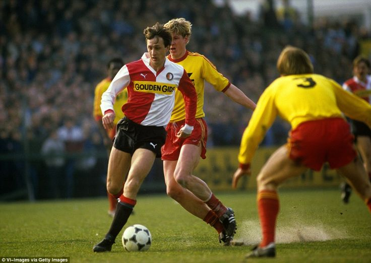 Cruyff (left) dribbles with the ball past Rene Smit (centre) during Feyenoord's match against the Go Ahead Eagles on March 18, 1984 at De Adelaarshorst Stadium in Deventer.