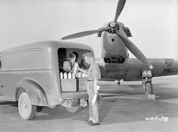 Armourers preparing to load practice bombs onto the wing racks of a Fairey Battle I aircraft... / Des armuriers se préparent à charger des bombes d'exercice dans les râteliers situés sous les ailes d'un avion Fairey Battle I... | by BiblioArchives / LibraryArchives