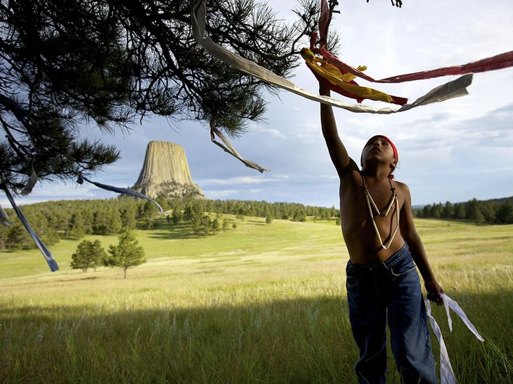 """This image appeared in """"America's Cathedrals,"""" an October 2013 Traveler story about ancient sacred places. Here, Wakinyan Two Bulls ties prayer flags on a tree in sight of Wyoming's Devils Tower, or Mato Tipila, long a sacred place for native peoples. Photograph by Aaron Huey, October 14, 2014"""